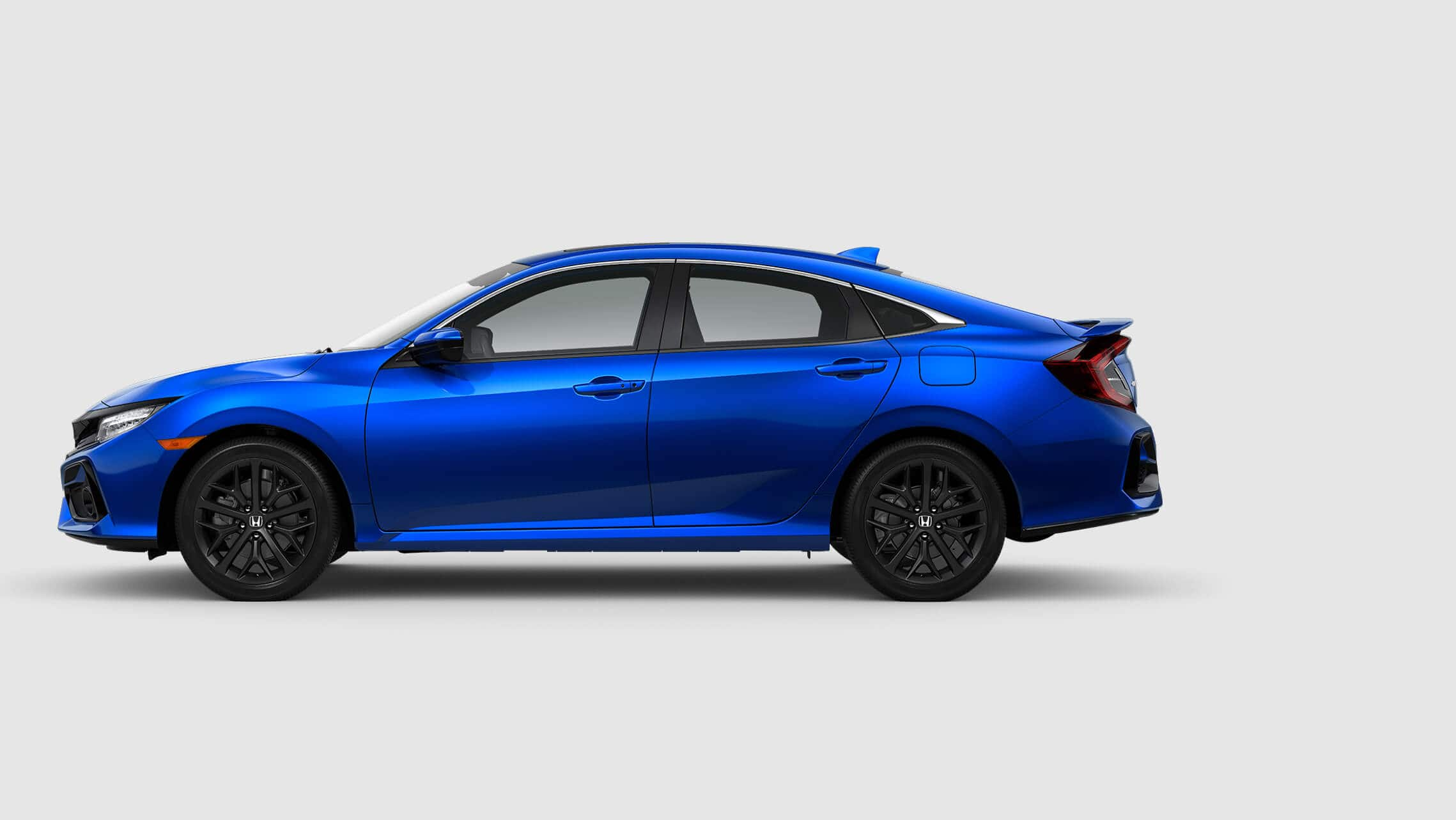 Rear 3/4 driver's side view of 2020 Honda Civic Si Sedan in Aegean Blue Metallic.