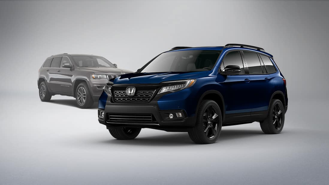 Passenger-side front 3/4 view of 2020 Honda Passport Elite, in Obsidian Blue Pearl, parked in studio environment next to Jeep Grand Cherokee.