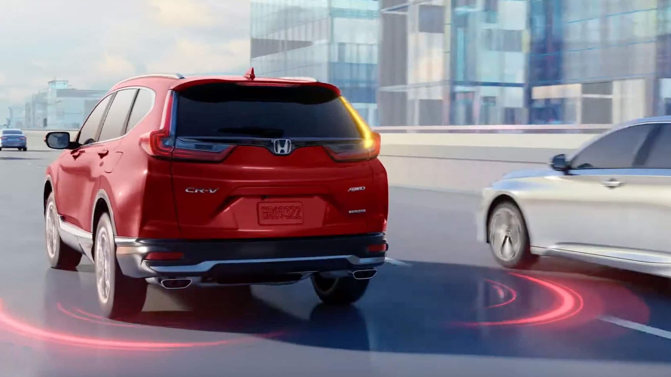 Rear driver-side view of the 2021 Honda CR-V in Radiant Red Metallic, driving on highway, with illustration showing blind spot information system feature.