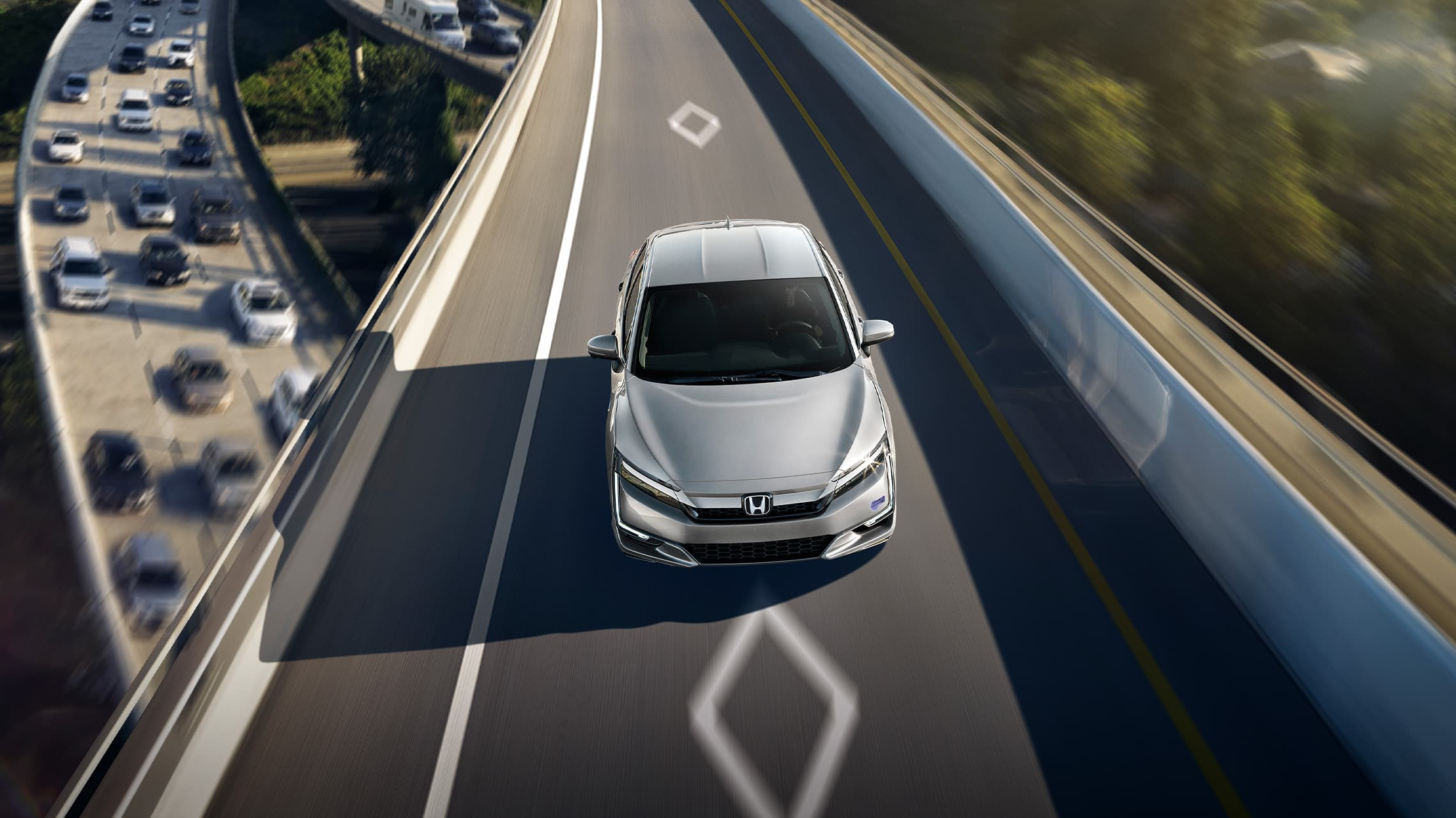 Front overhead of 2021 Clarity Plug-In Hybrid in Solar Silver Metallic driving on HOV access lane.